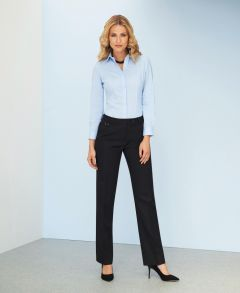Woman Wearing A Light Blue Long Sleeve Blouse And Navy Tailored Leg Business Trousers